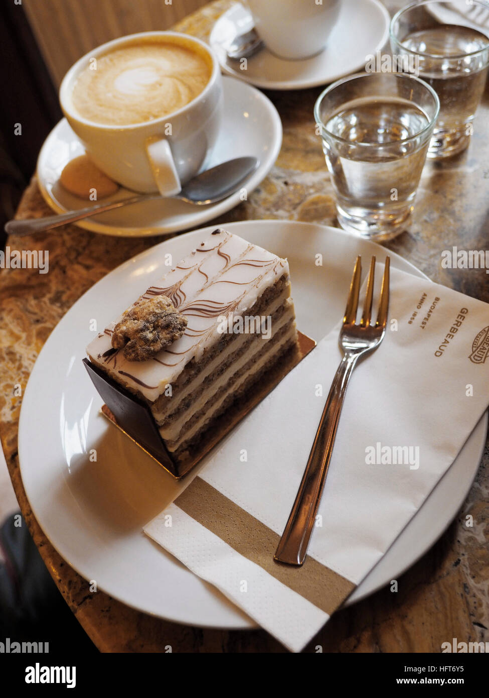 Esterhazy torte cake and cappuccino at Gerbeaud kavehaz in Budapest, Hungary. - Stock Image