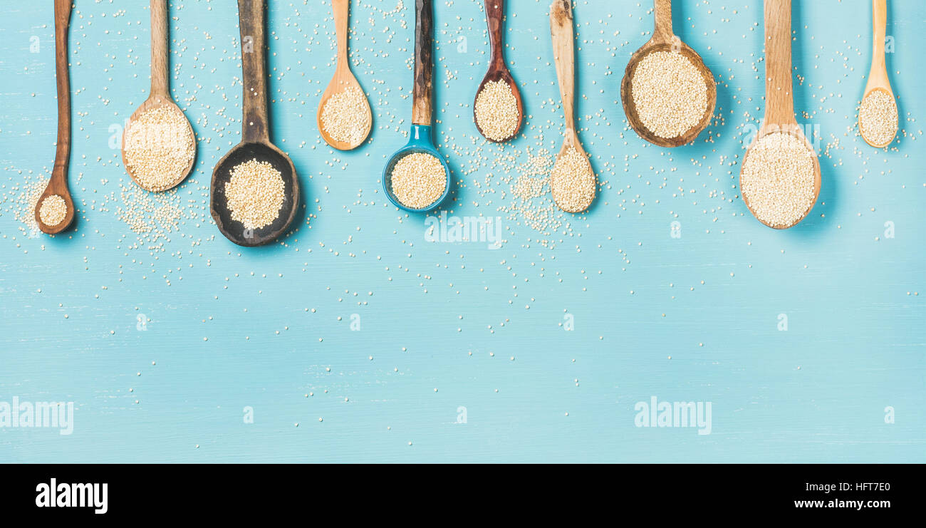 Quinoa seeds in different spoons over light blue background - Stock Image