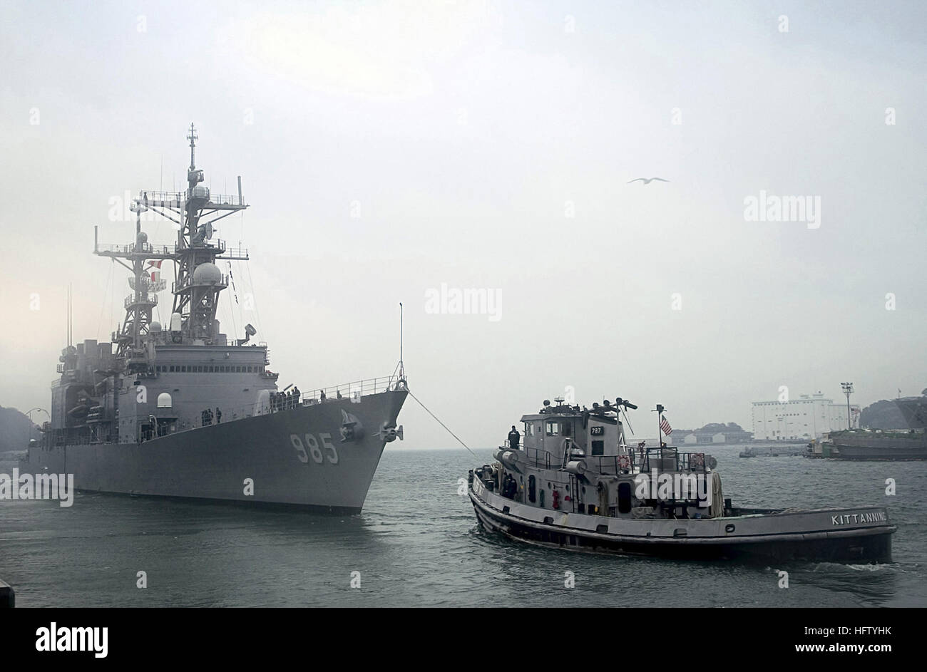 The US Navy (USN) Spruance Class Destroyer, USS CUSHING (DD 985) is pushed out to sea from Commander Fleet Activities - Stock Image
