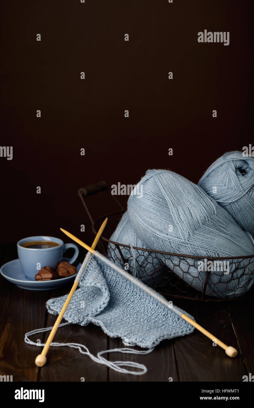 Knitting from light blue yarn. Cup of coffee and chocolates. - Stock Image