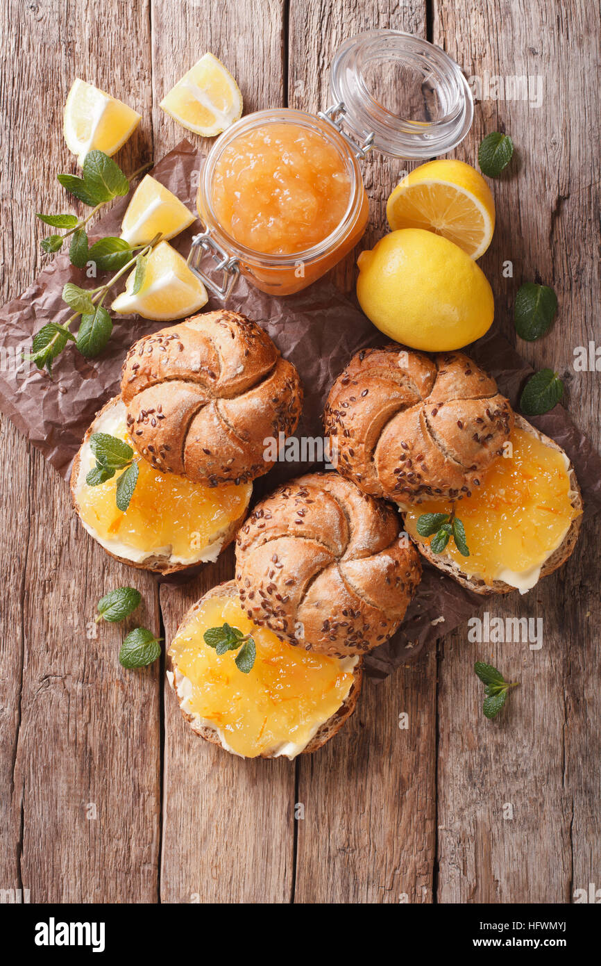 Sweet buns with lemon marmalade and butter on the table. vertical view from above - Stock Image