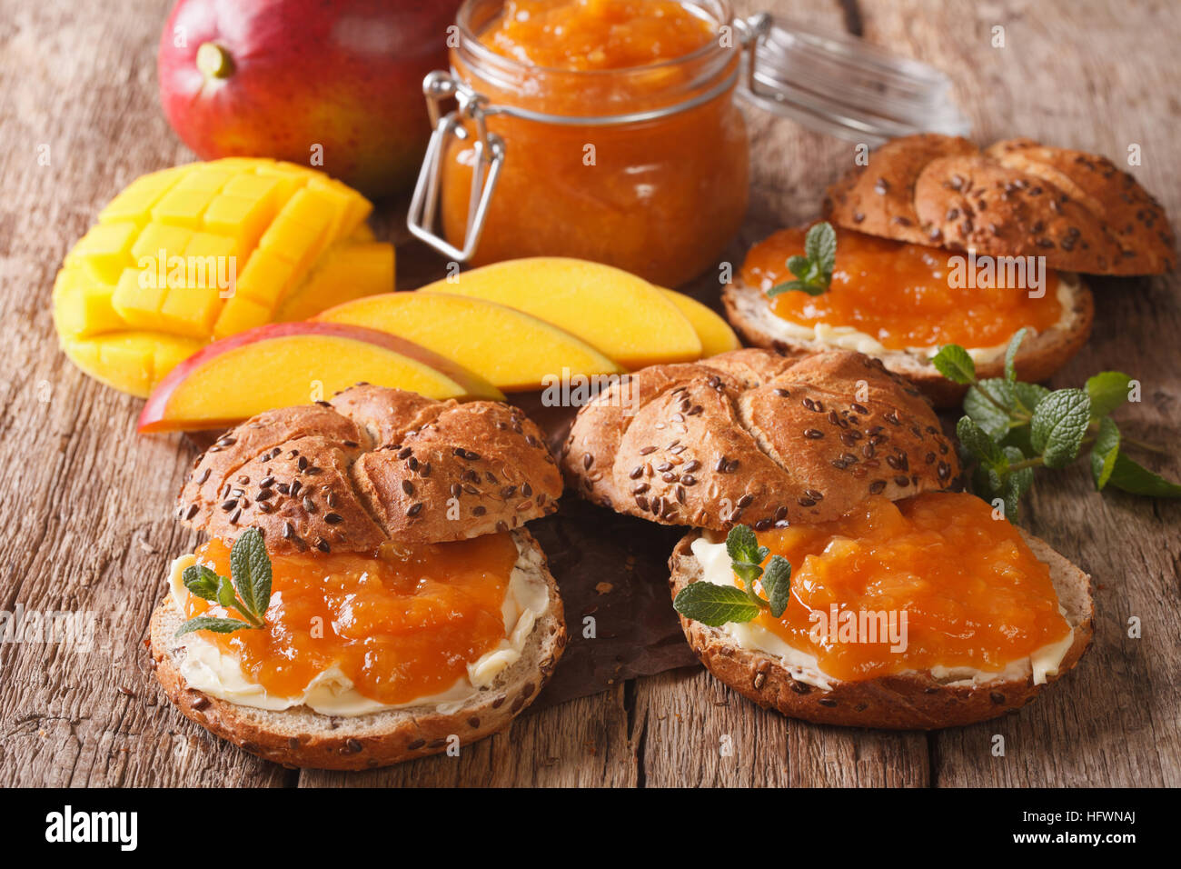 Tasty sandwiches with mango confiture, butter and mint close-up on the table. horizontal - Stock Image