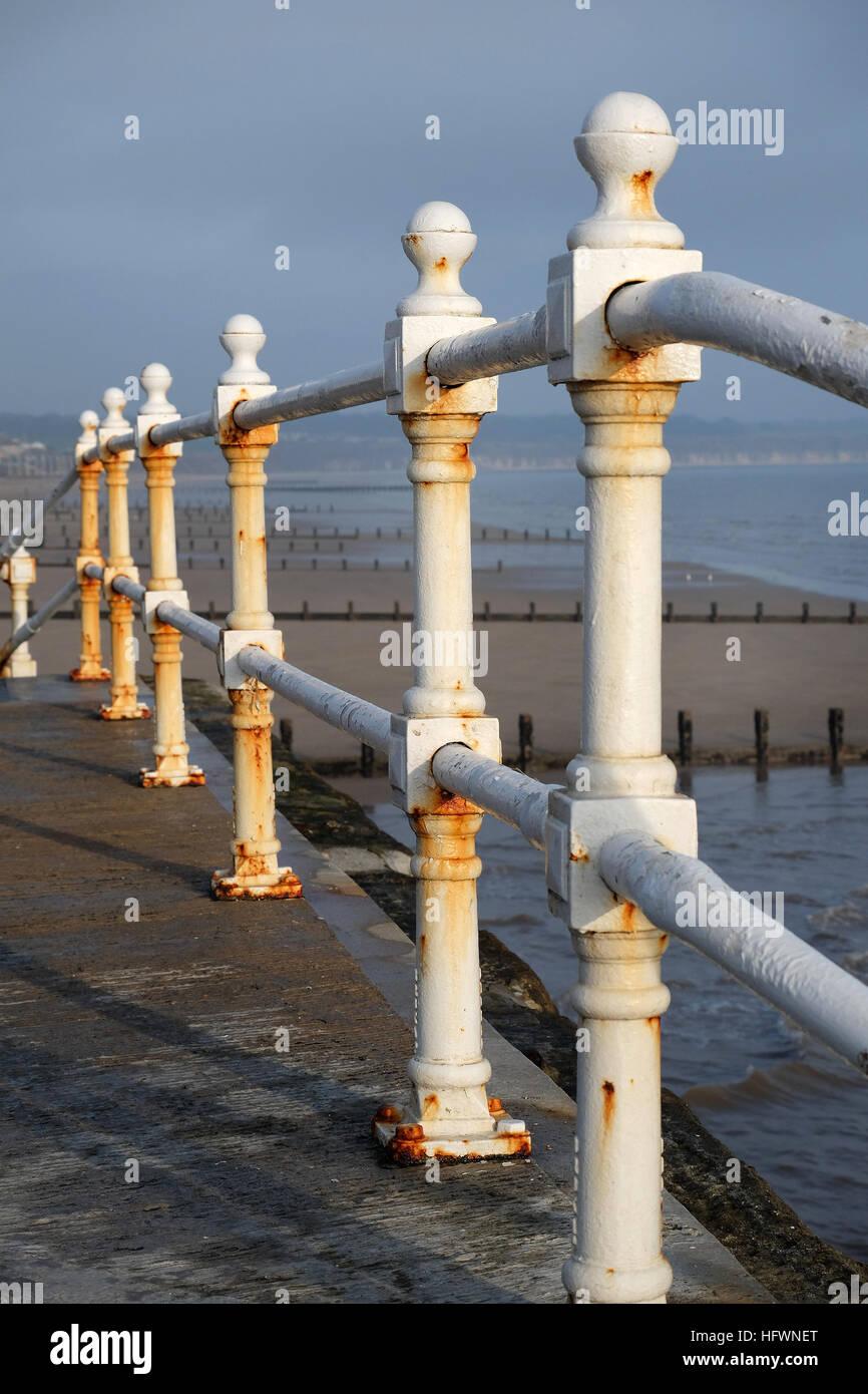 Corrosion on white painted cast iron railings at seaside resort. - Stock Image