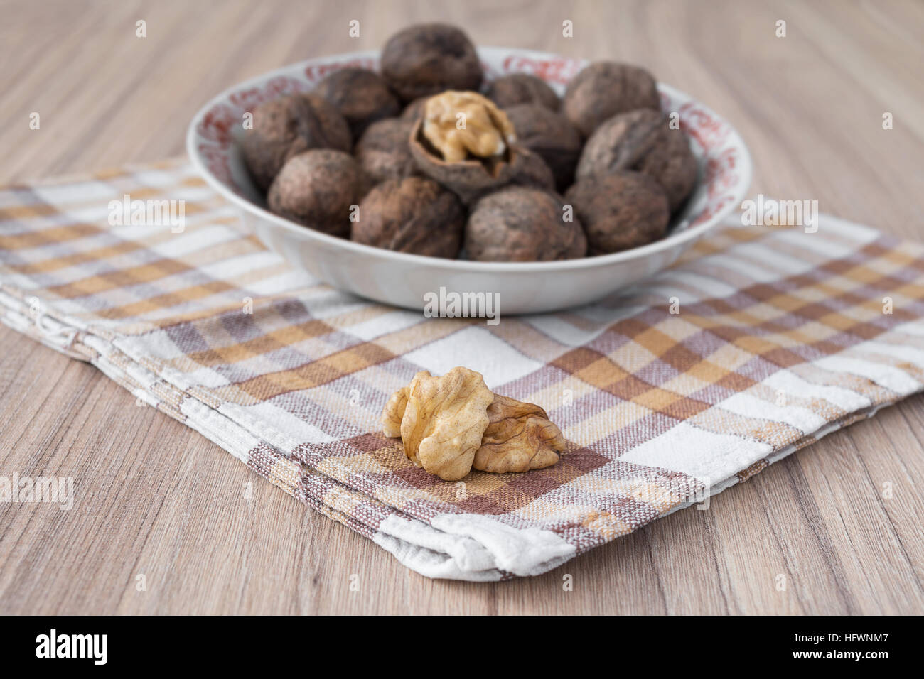 Whole walnuts and walnut kernels in white plate on table with checkered tablecloth - Stock Image