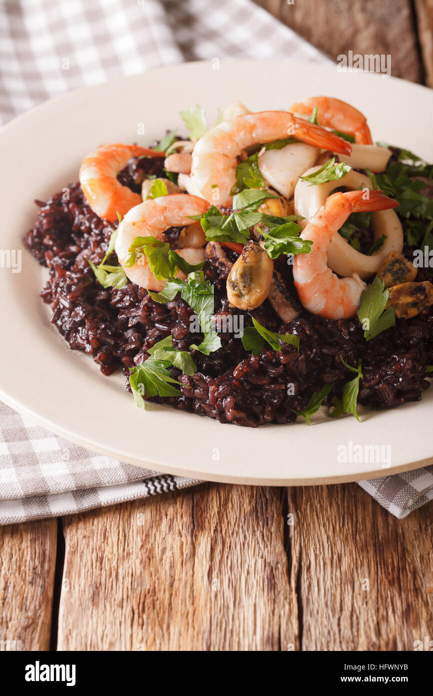 Black rice with shrimp, calamari, mussels and scallops on the plate closeup. vertical - Stock Image