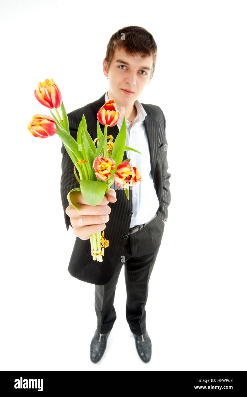 A young man in a black suit with five red tulips - Stock Image