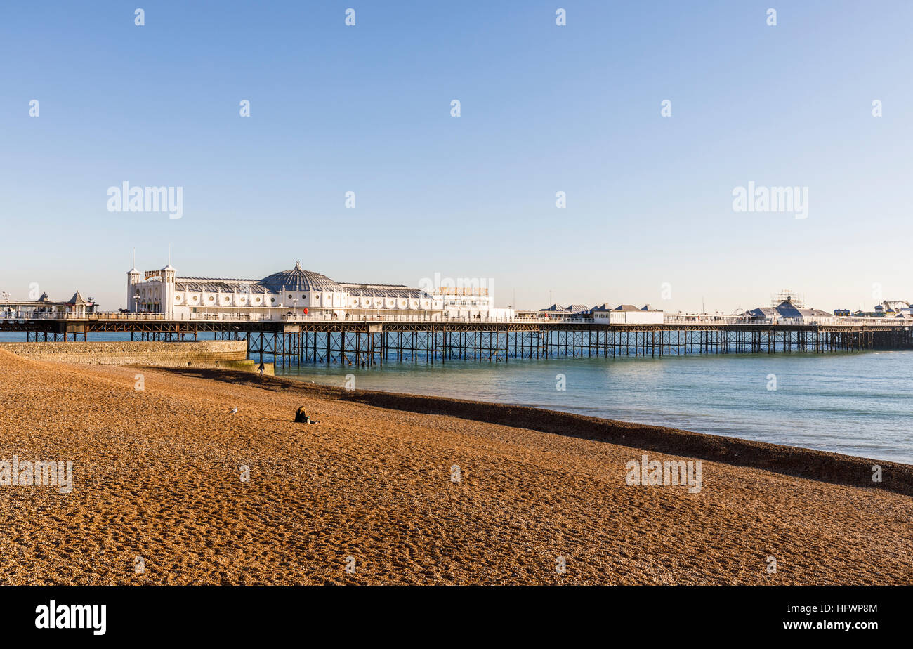 The Victorian Brighton Palace Pier and shingle Brighton beach deserted on a sunny winter day in November with blue - Stock Image
