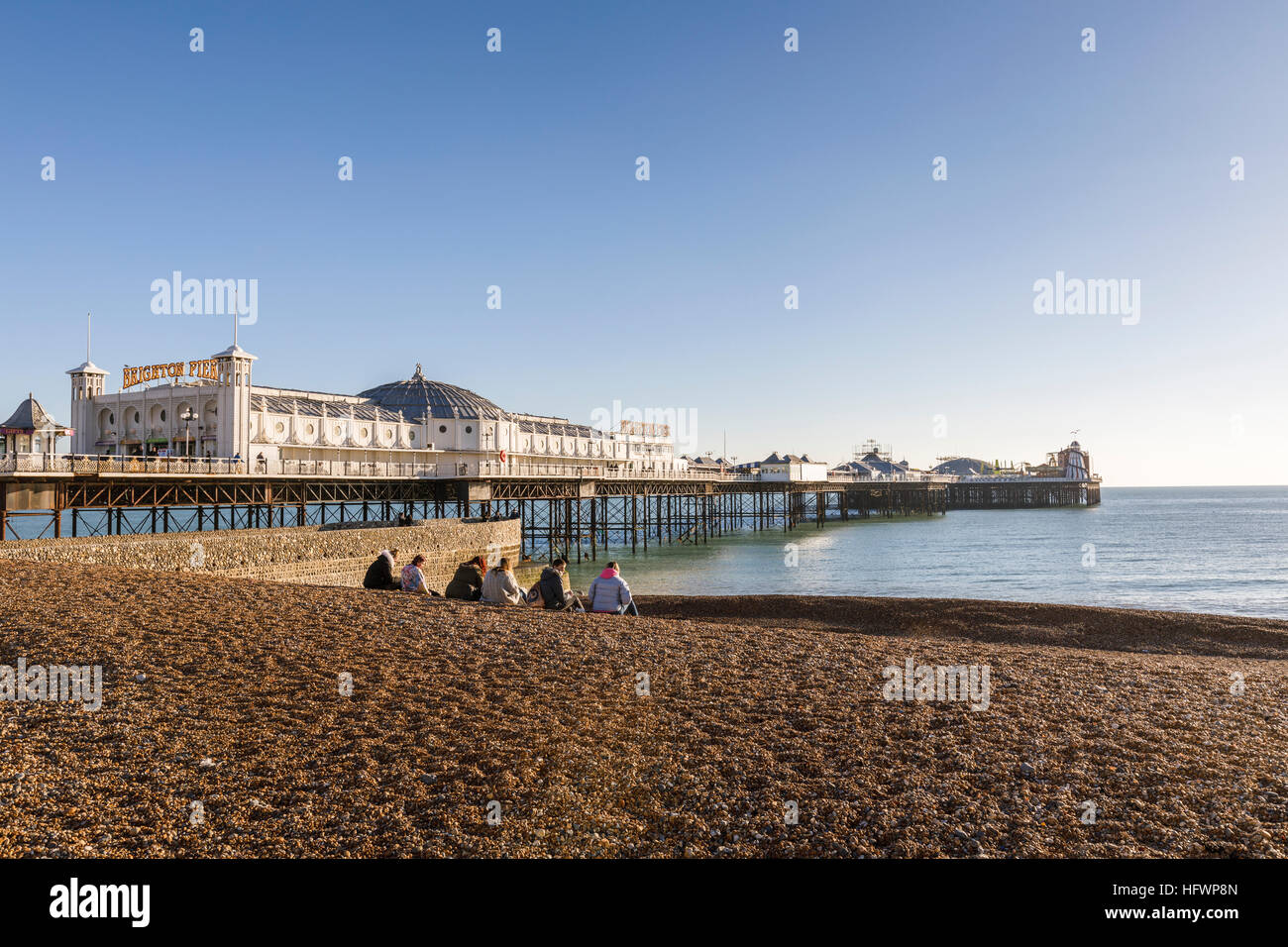 The Victorian Brighton Palace Pier and shingle Brighton beach with a small group on a sunny winter day in November - Stock Image