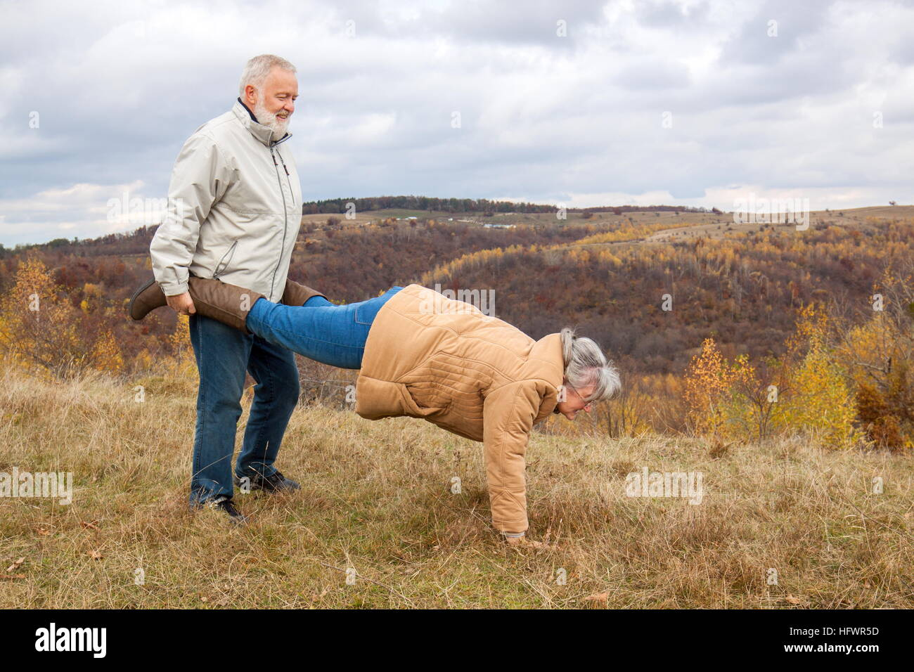 Elderly Couple Having Fun And Playing The Wheelbarrow In Nature