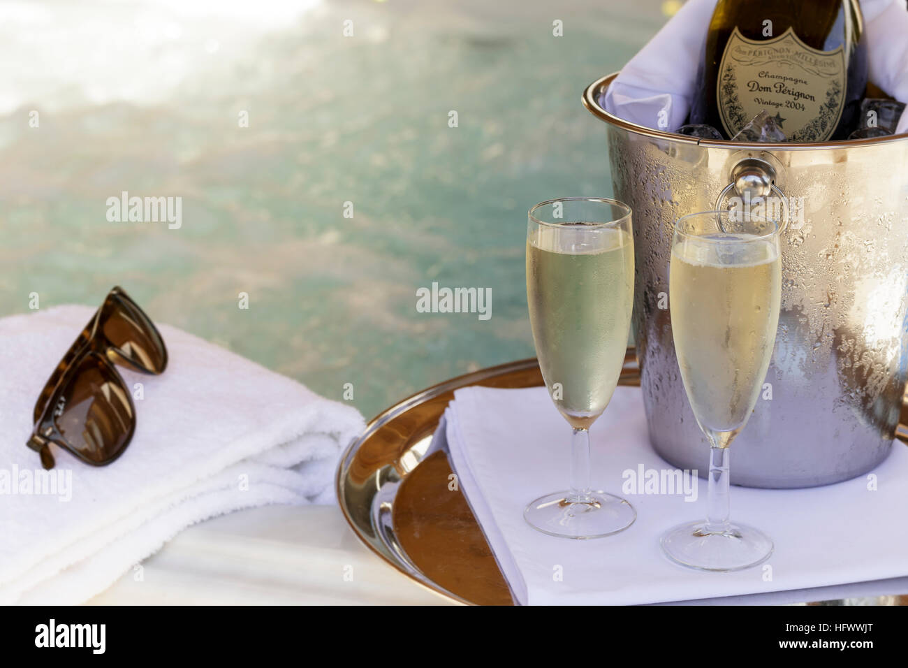 Champagne bottle and flutes with jacuzzi behind - Stock Image