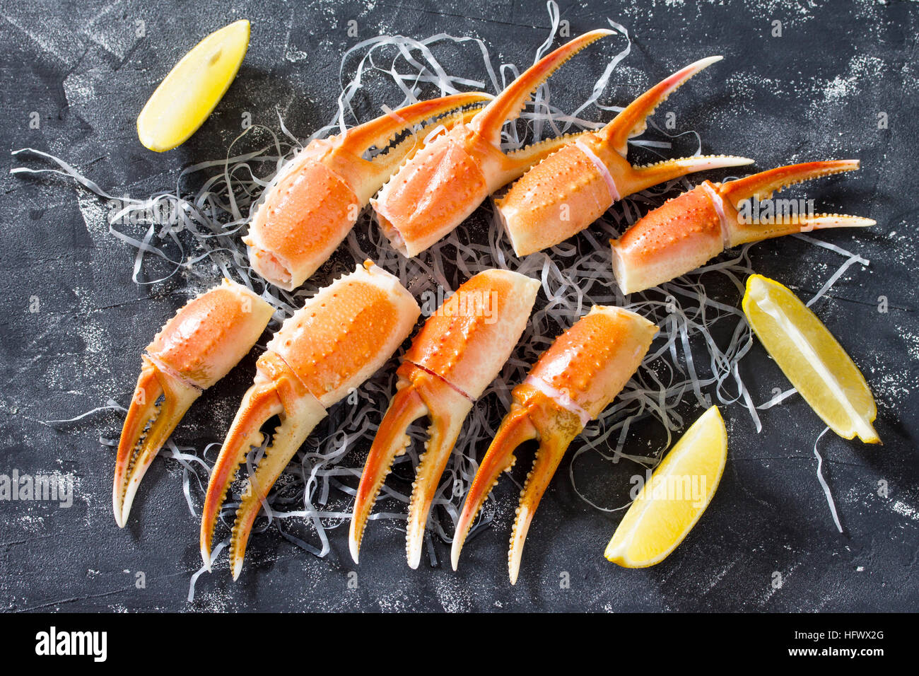 Cooked crab claws with lemon, sea salt and pepper on a concrete background - concept of healthy eating, dieting Stock Photo