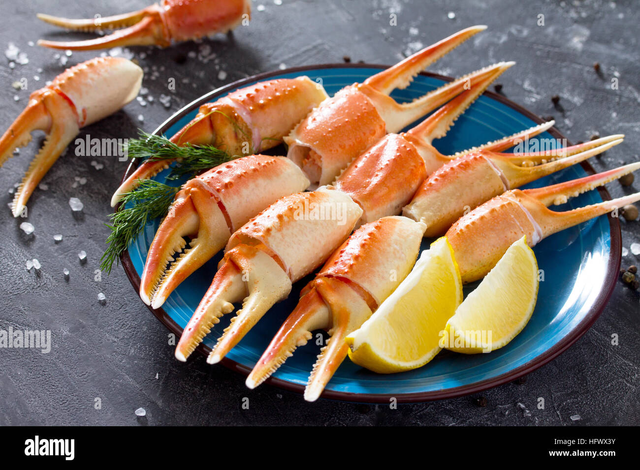 Cooked crab claws with lemon, sea salt and pepper on a concrete background. - Stock Image