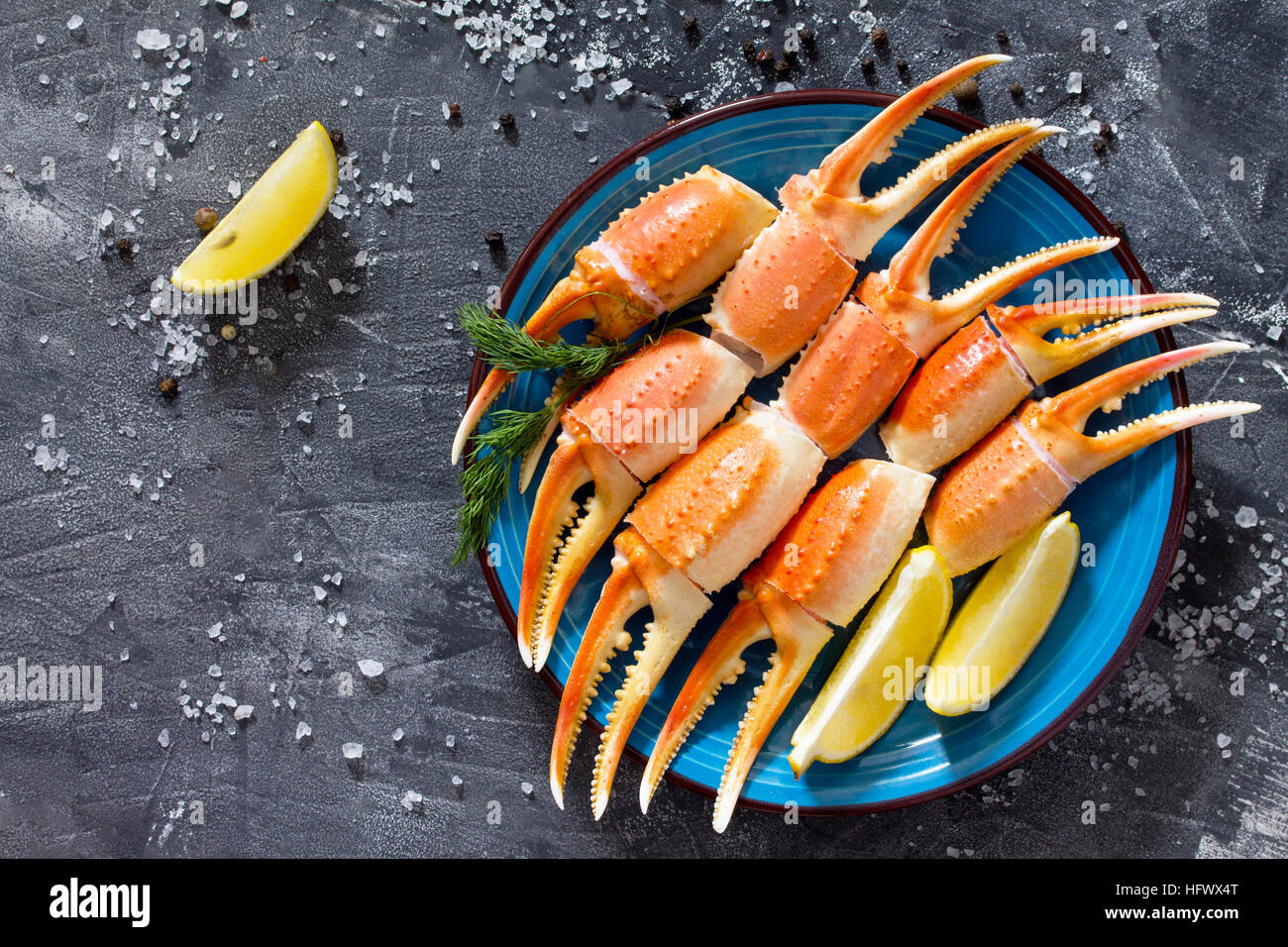 Cooked crab claws with lemon, sea salt and pepper on a concrete background - concept of healthy eating, dieting - Stock Image