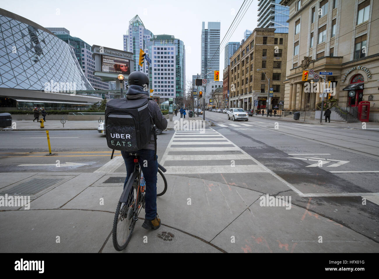 TORONTO, CANADA - DECEMBER 31, 2016: Uber Eats delivery man on a bicycle waiting to cross a street - Stock Image