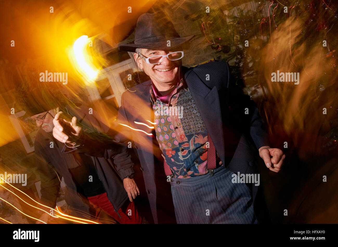 Middle aged man dancing at party dressed in braces and having fun - Stock Image