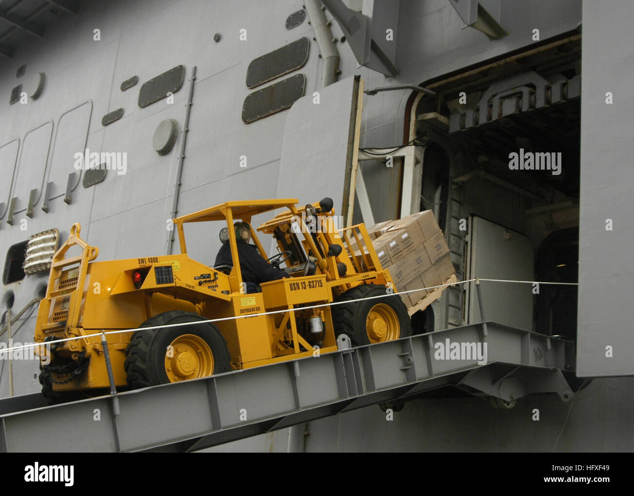 051021-N-3527B-064 Norfolk, Virginia (October 21, 2005) - A crew member moves supplies up the ramp of the amphibious - Stock Image