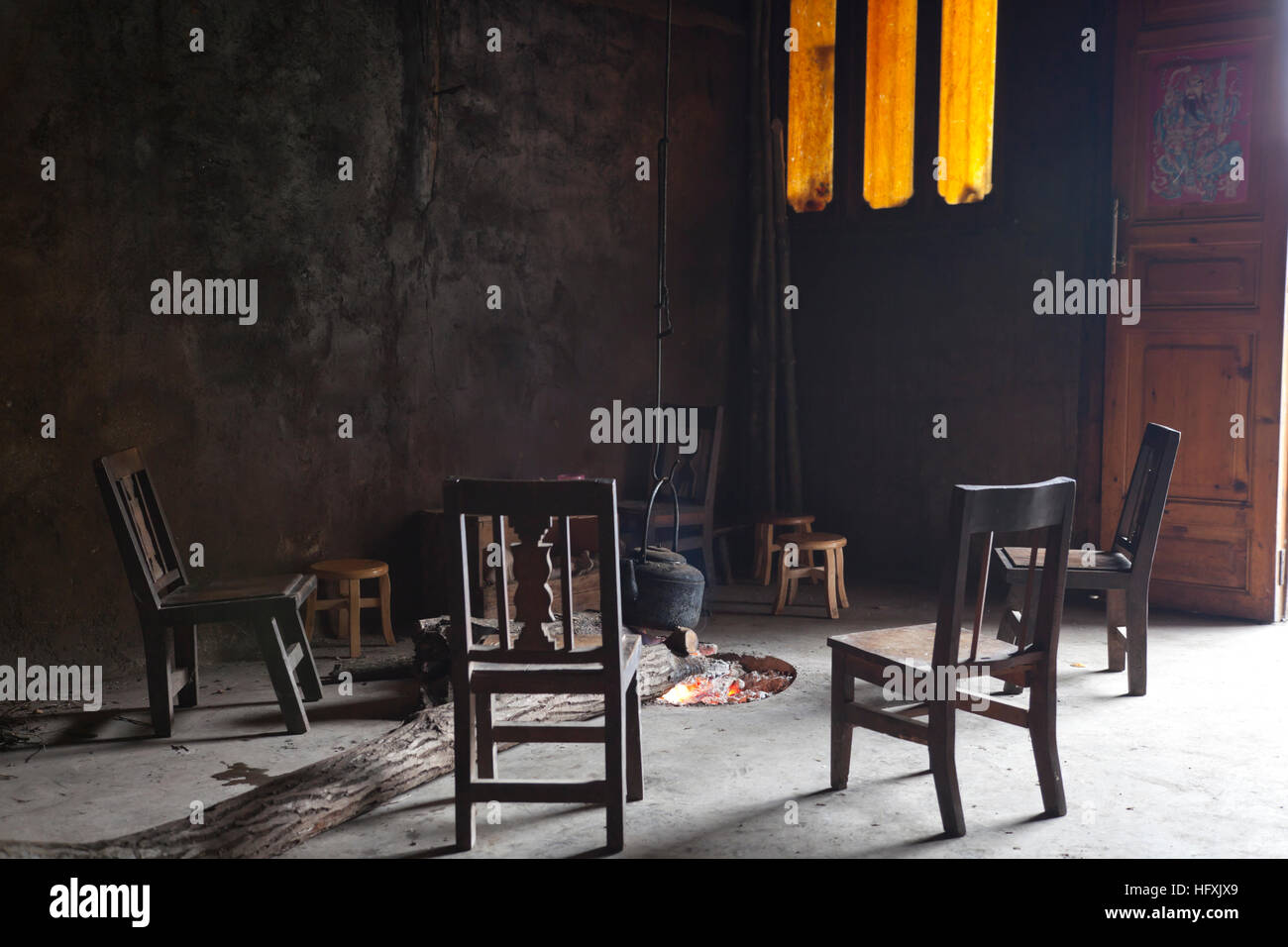 Homemade chairs set around an open log fire in the open living room of a farmhouse in a remote village in west China. - Stock Image