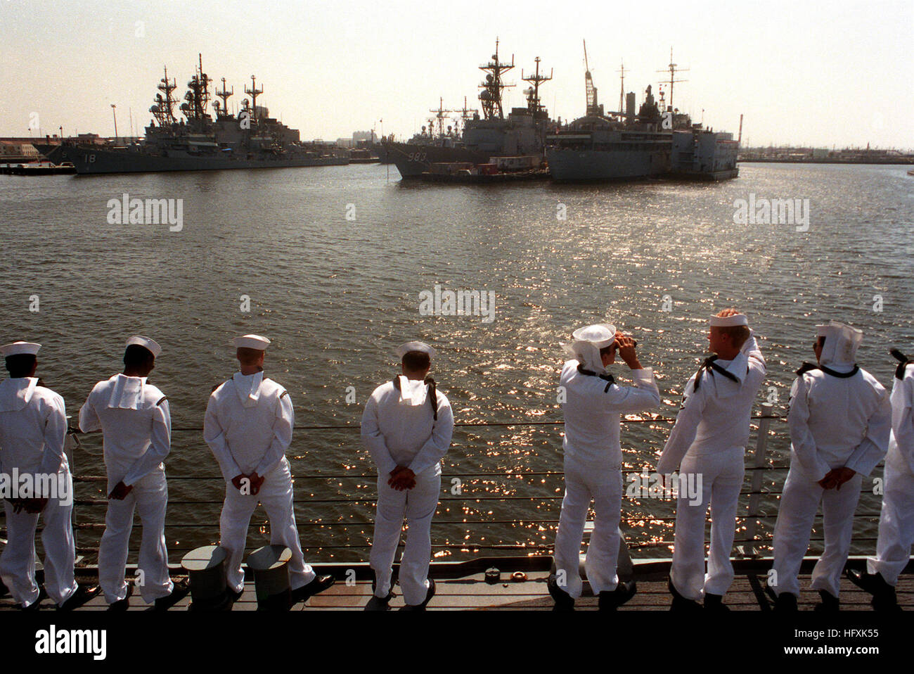 Crew members man the rails aboard the guided missile frigate USS NICHOLAS (FFG-47) as the vessel passes the destroyer - Stock Image