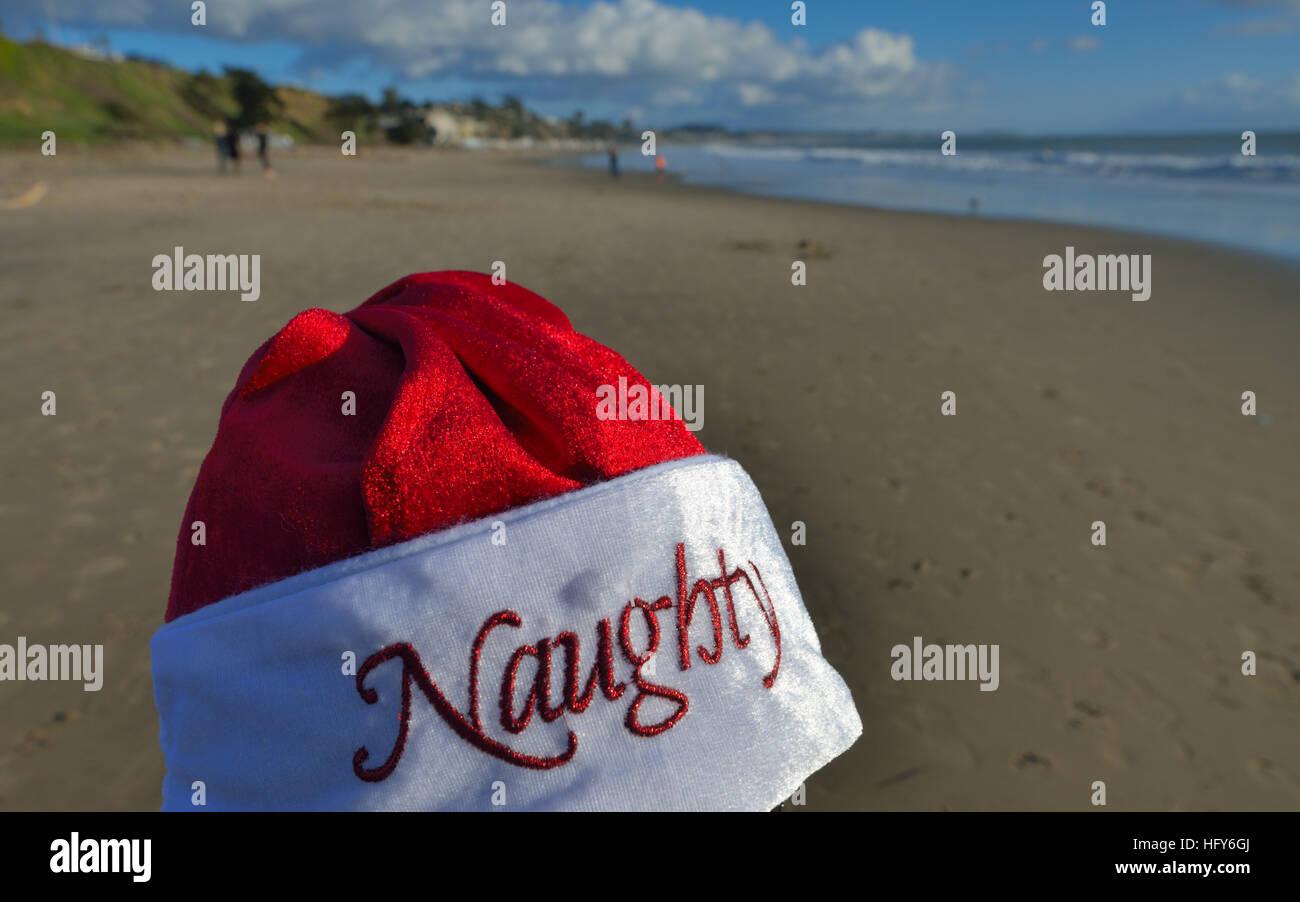 Naughty Santa Claus at Christmas on the Seacliff state beach, Aptos CA - Stock Image