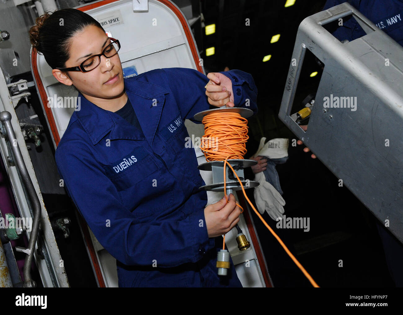 110405-N-3154P-155  MEDITERRANEAN SEA (April 5, 2011) Damage Controlman Fireman Vanessa Duenas unrolls cable for - Stock Image