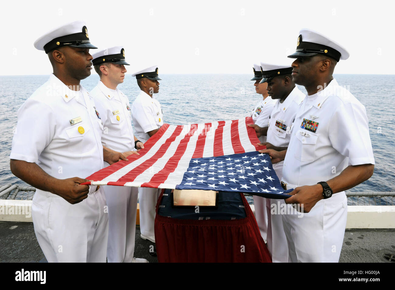 110818-N-AU622-013 ATLANTIC OCEAN (Aug. 18, 2011) Chief petty officers prepare a flag for a burial at sea aboard - Stock Image