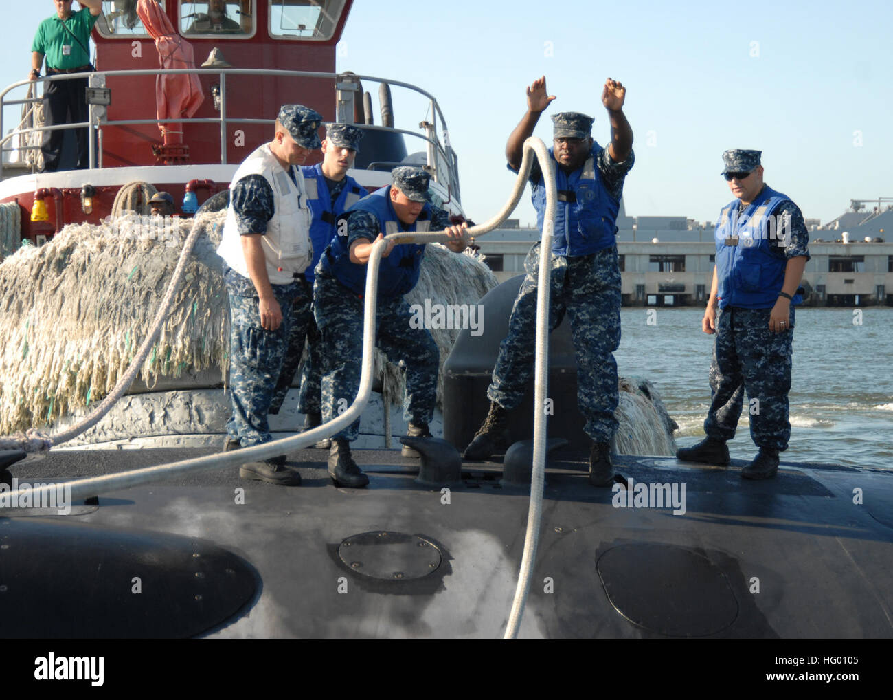 110825-N-NK458-008 NORFOLK (Aug. 25, 2011) Sailors aboard a Los Angeles-class attack submarine casts away mooring - Stock Image