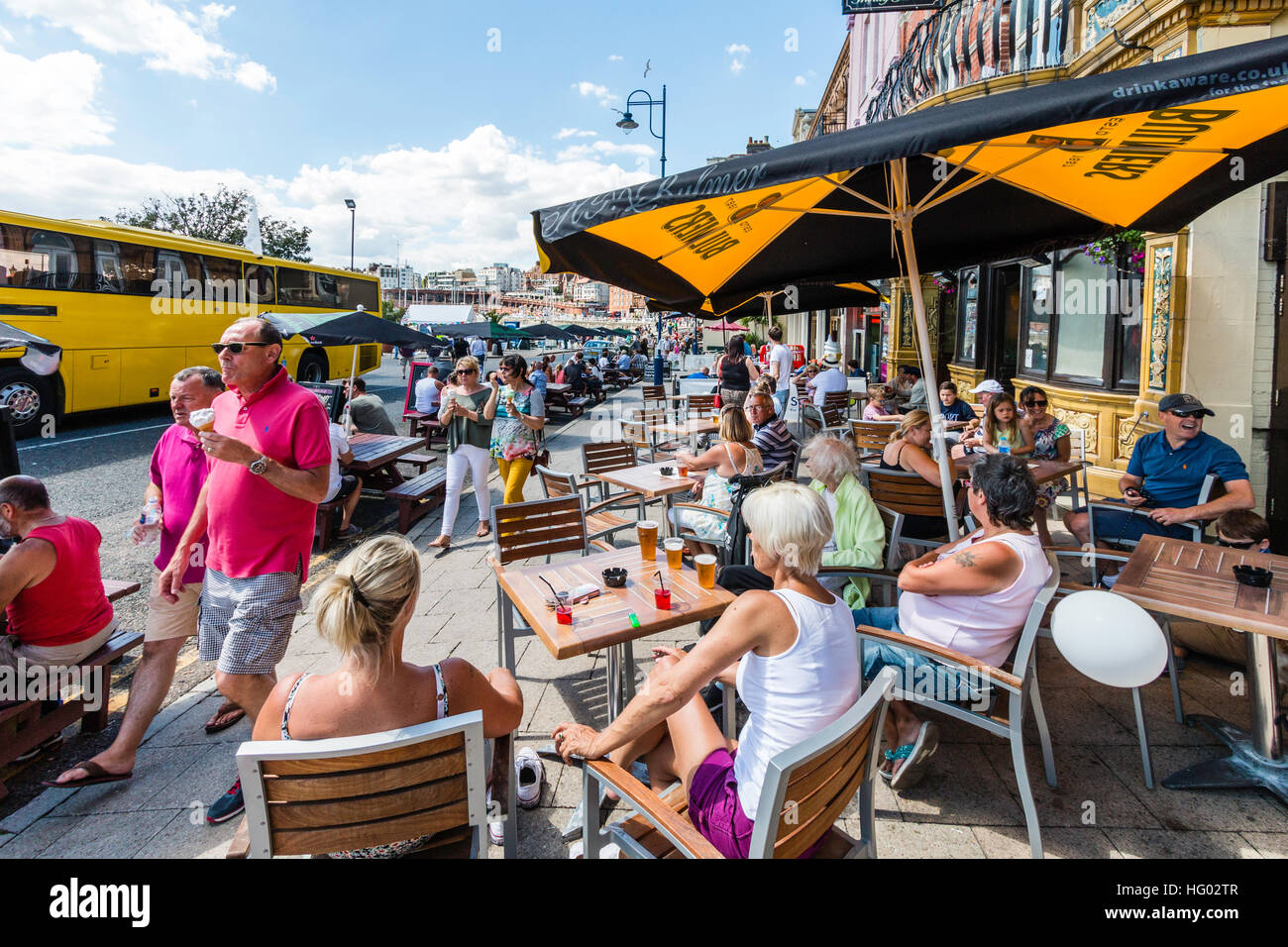 English seafront at Ramsgate with people sitting at tables and chairs under parasols, enjoying drinks during very - Stock Image