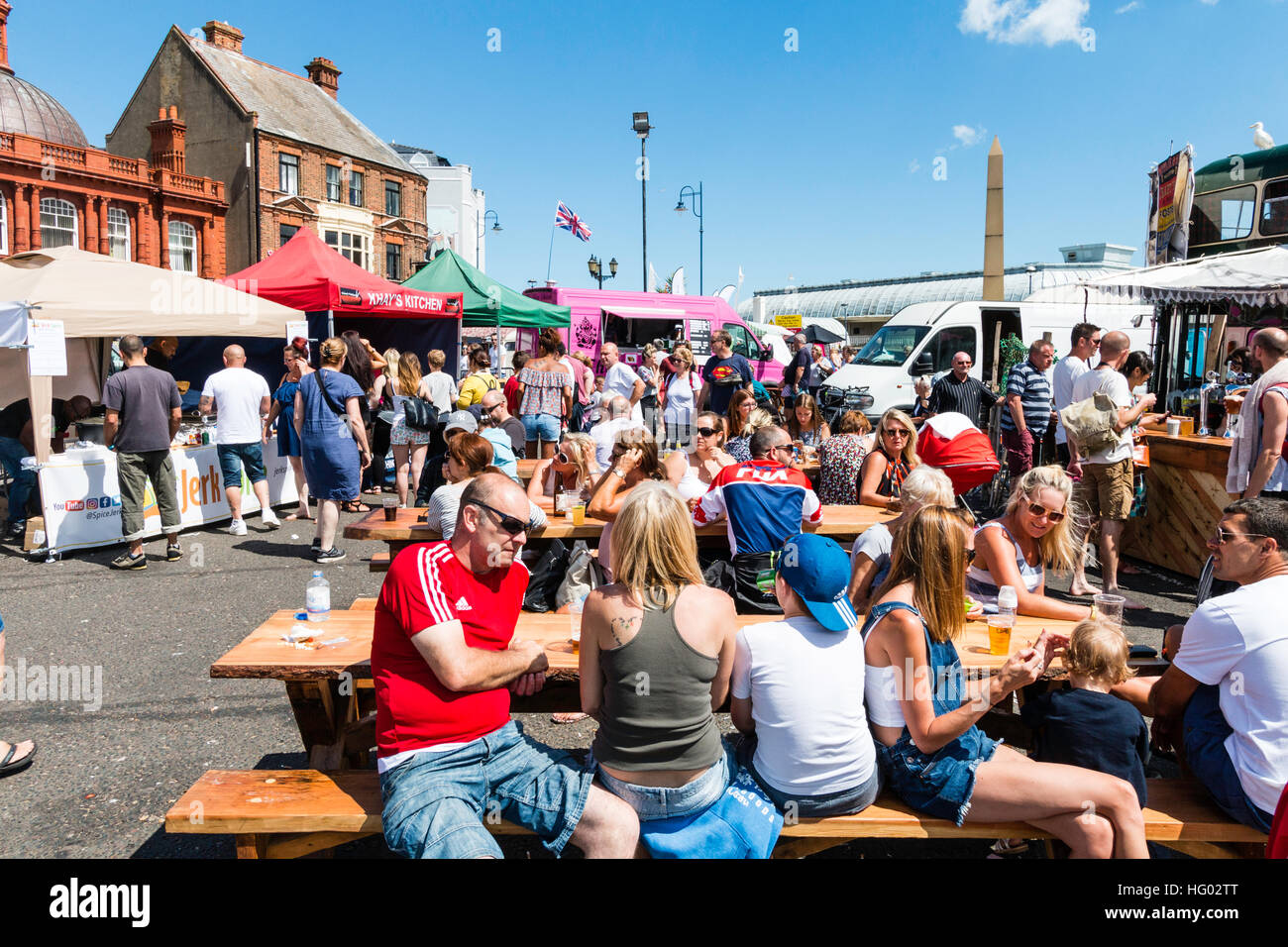 English seafront at Ramsgate with people sitting at tables and chairs enjoying drinks during very hot weather in - Stock Image