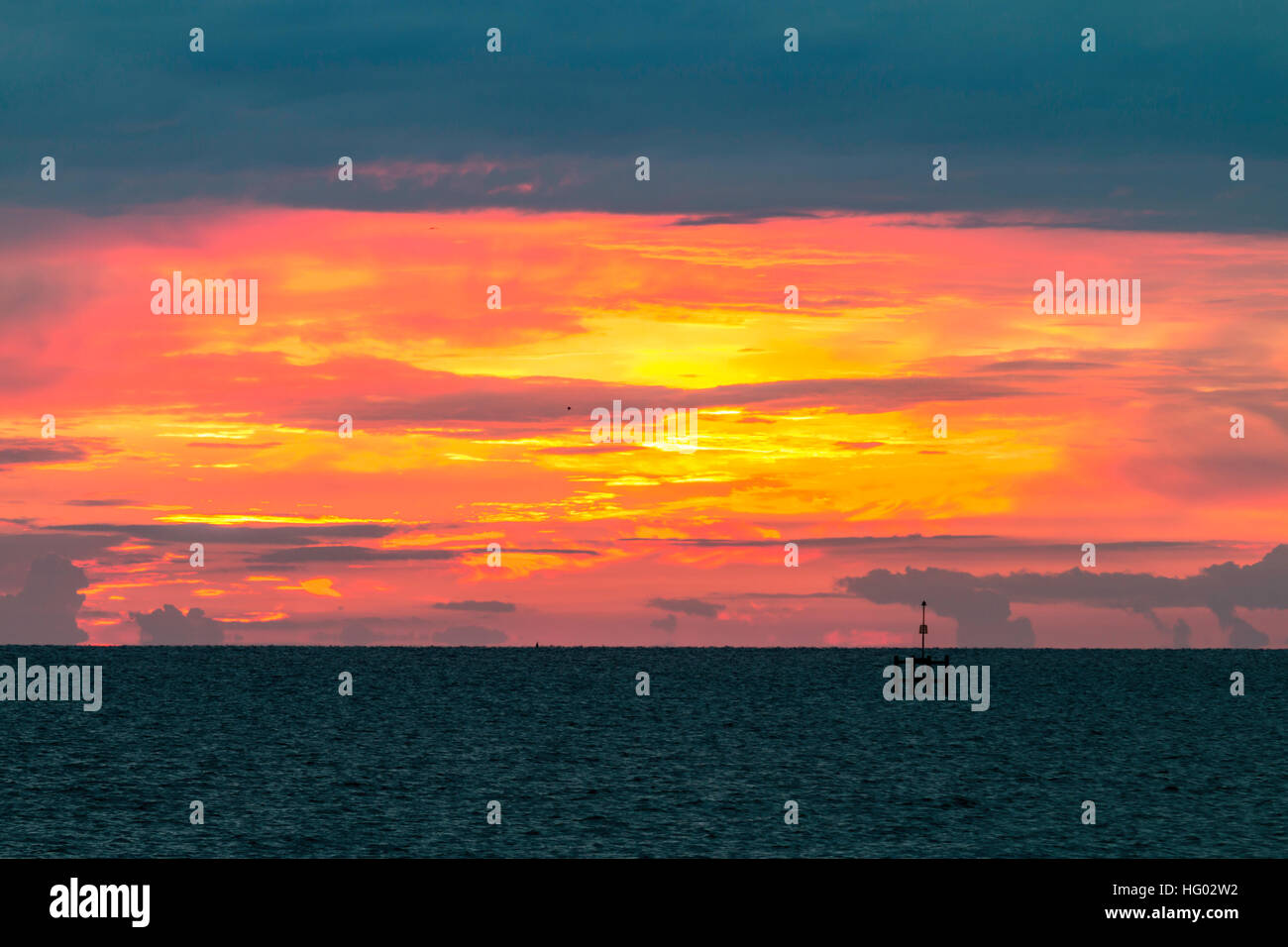 England, Herne Bay. English Channel at day break, dramatic orange and yellow sky on horizon with dark clouds above. - Stock Image
