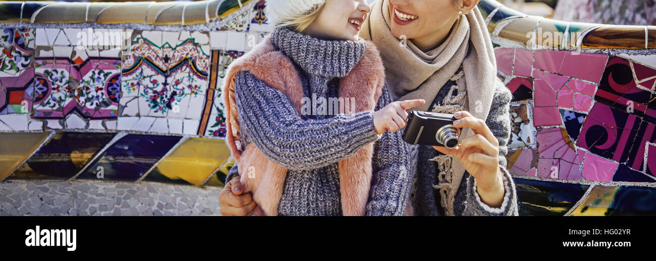 Barcelona signature style. Closeup on happy trendy mother and child travellers in Barcelona, Spain viewing photos - Stock Image