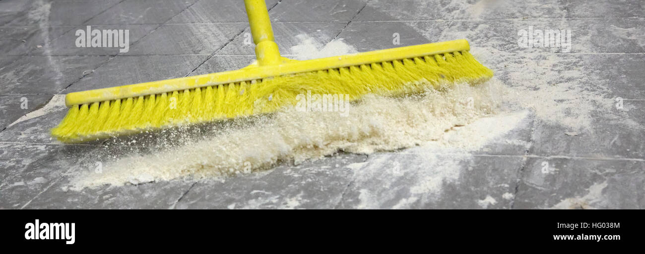 Sweeping the bakery floor from flour residue - Stock Image