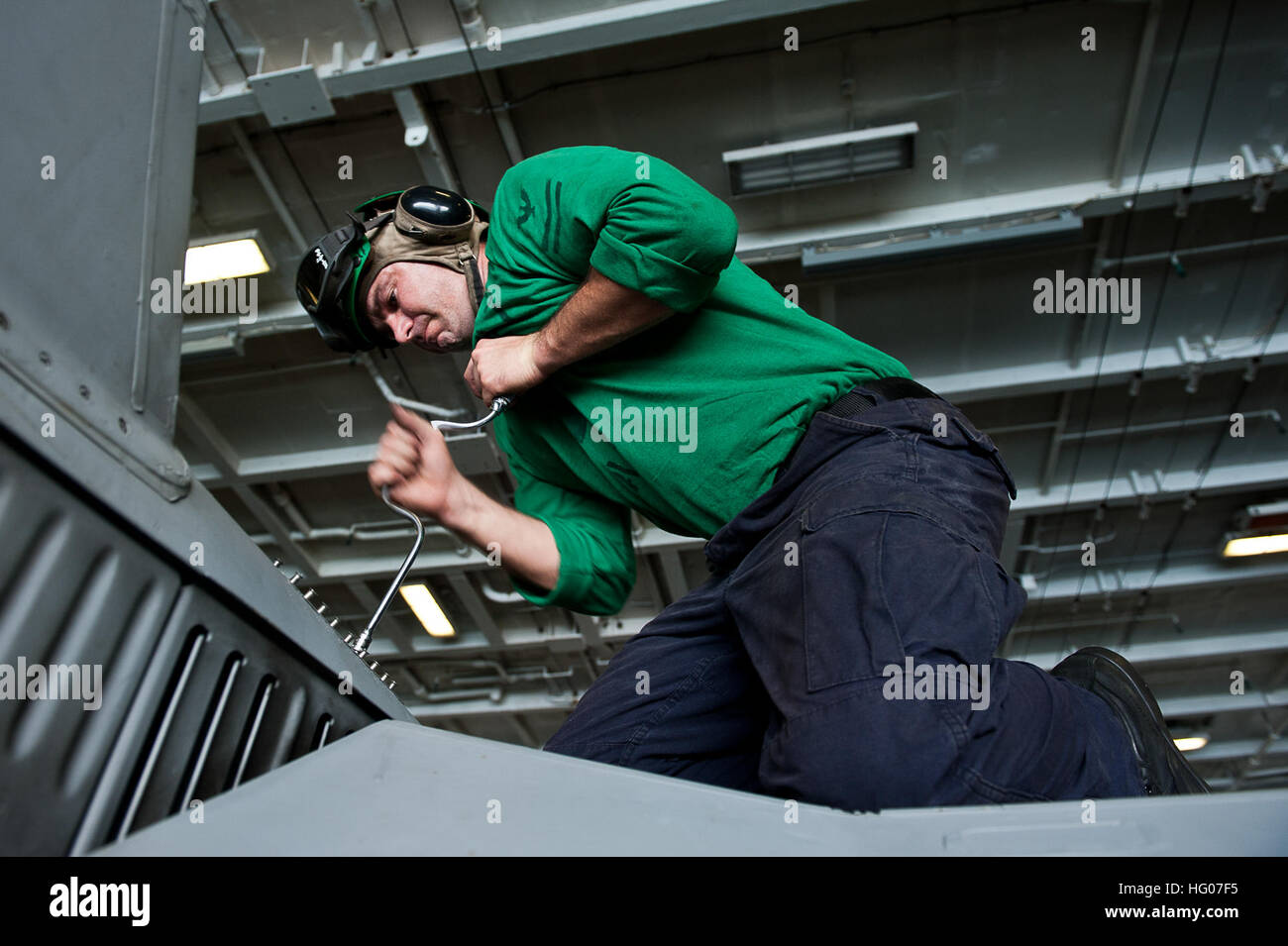 111019-N-BT887-028 ARABIAN SEA (Oct. 19, 2011) Aviation Structural Mechanic 2nd Class Craig Heady removes a panel - Stock Image