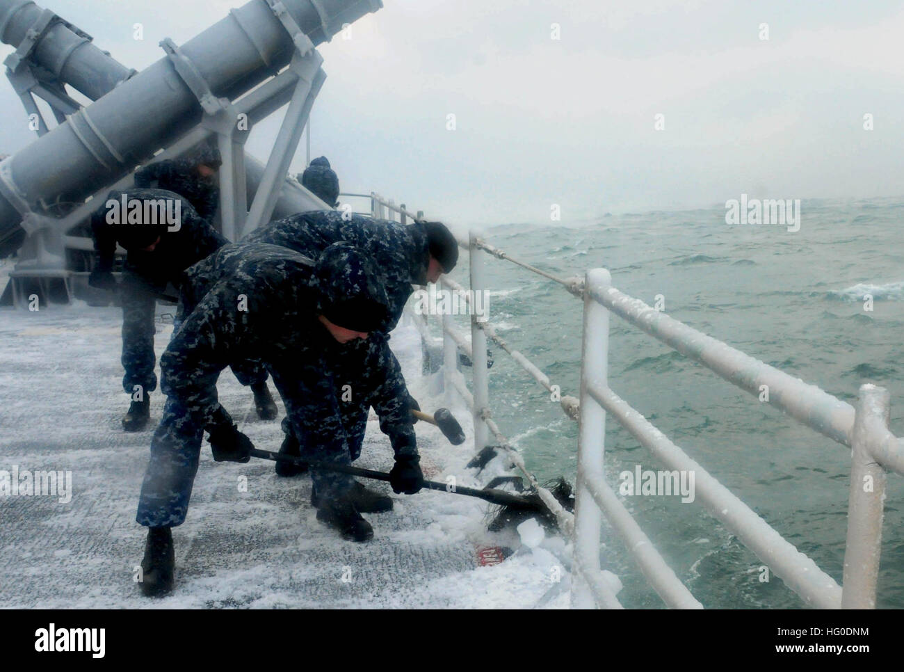 Sailors aboard the guided-missile cruiser USS Vella Gulf sweep snow and ice off of the ship in the Black Sea. Vella Stock Photo