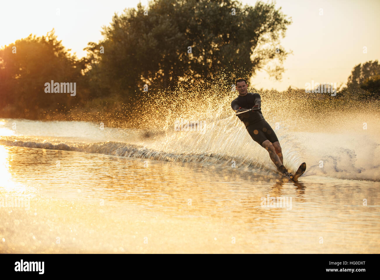 Man wakeboarding on a lake with splashes of water. Wakeboarder surfing across the lake. - Stock Image