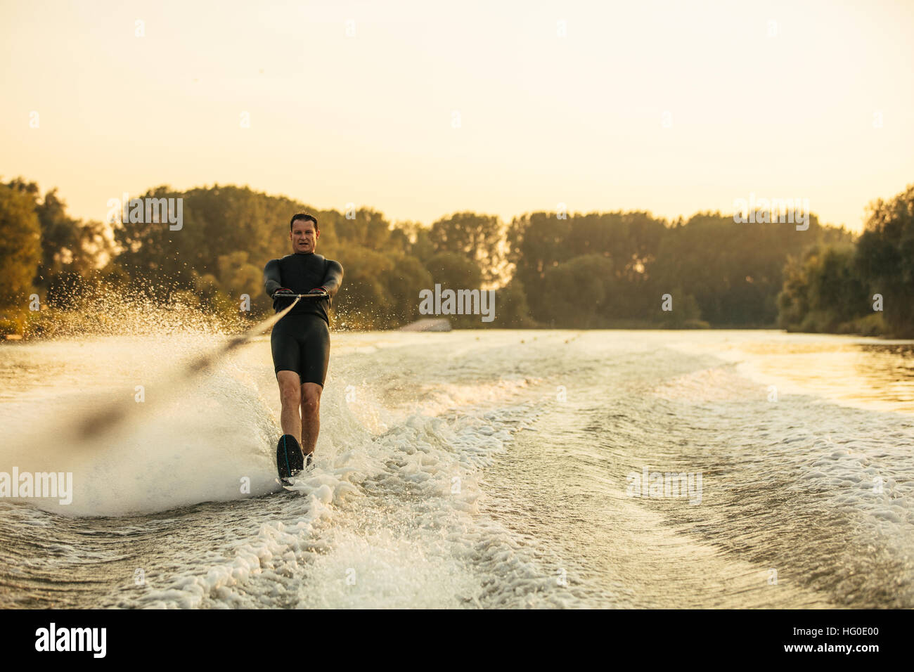 Man riding wakeboard on wave of motorboat. Male water skiing behind a boat on lake. - Stock Image