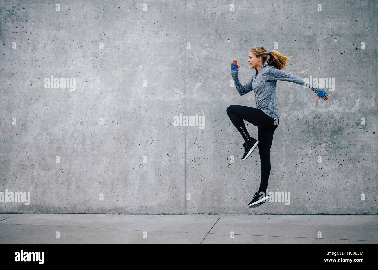Side view shot of fit young woman doing cardio interval training against grey background. Fitness female exercising - Stock Image