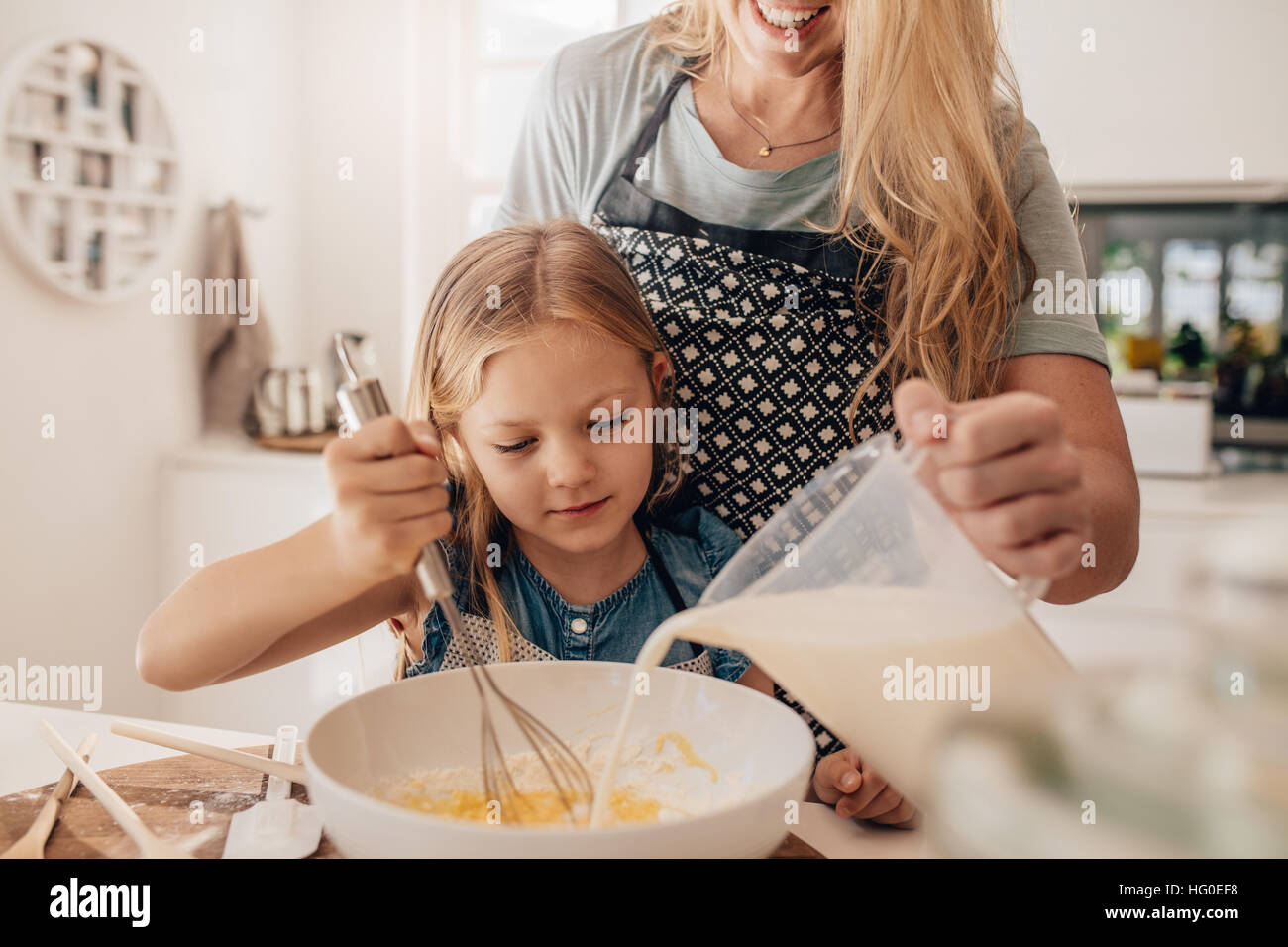 Cute little girl and her mother mixing batter in the bowl. Mother pouring milk with daughter whisking the batter. - Stock Image