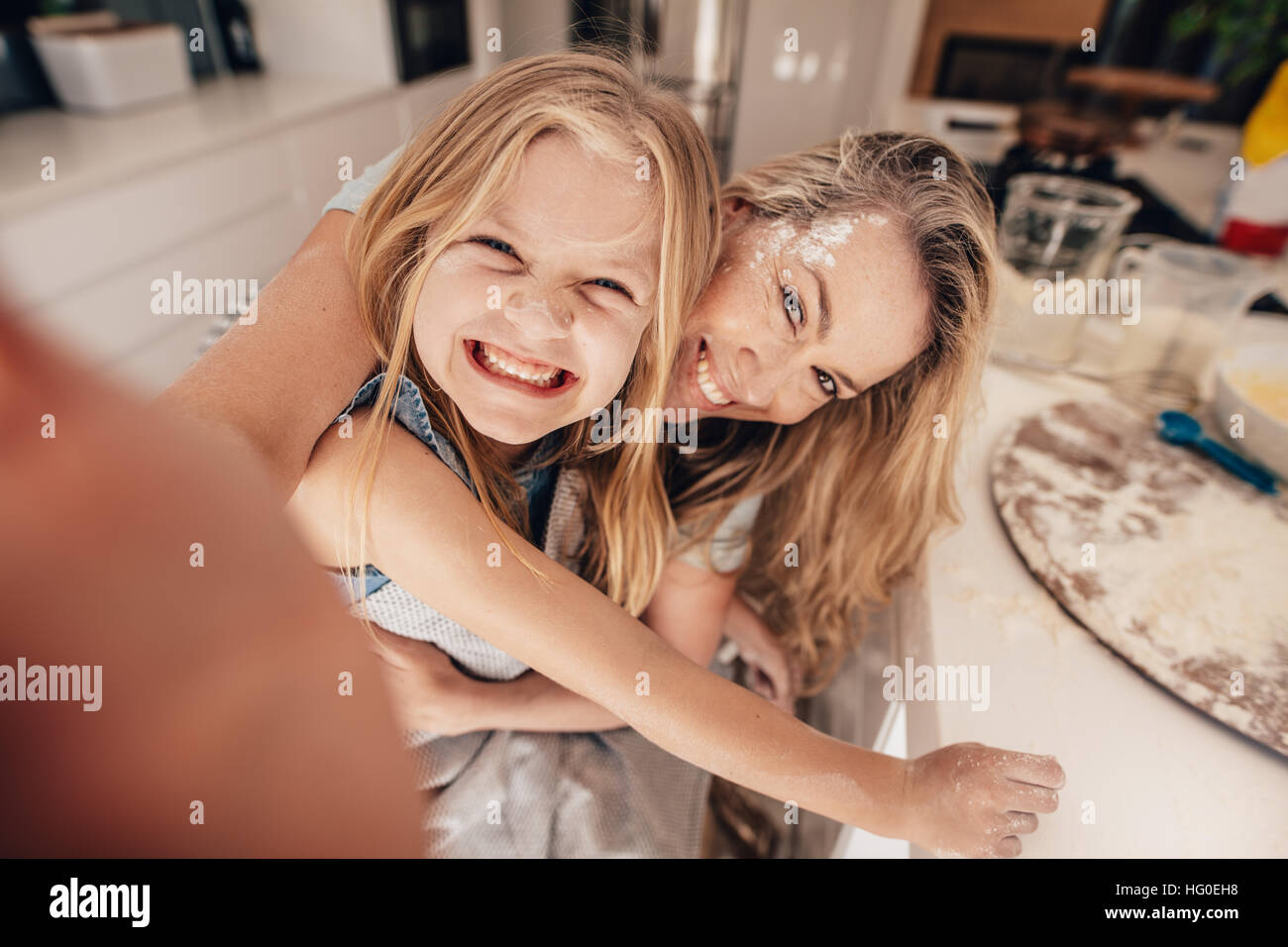 Smiling little girl and woman in kitchen taking selfie. Happy young mother and daughter cooking food. - Stock Image