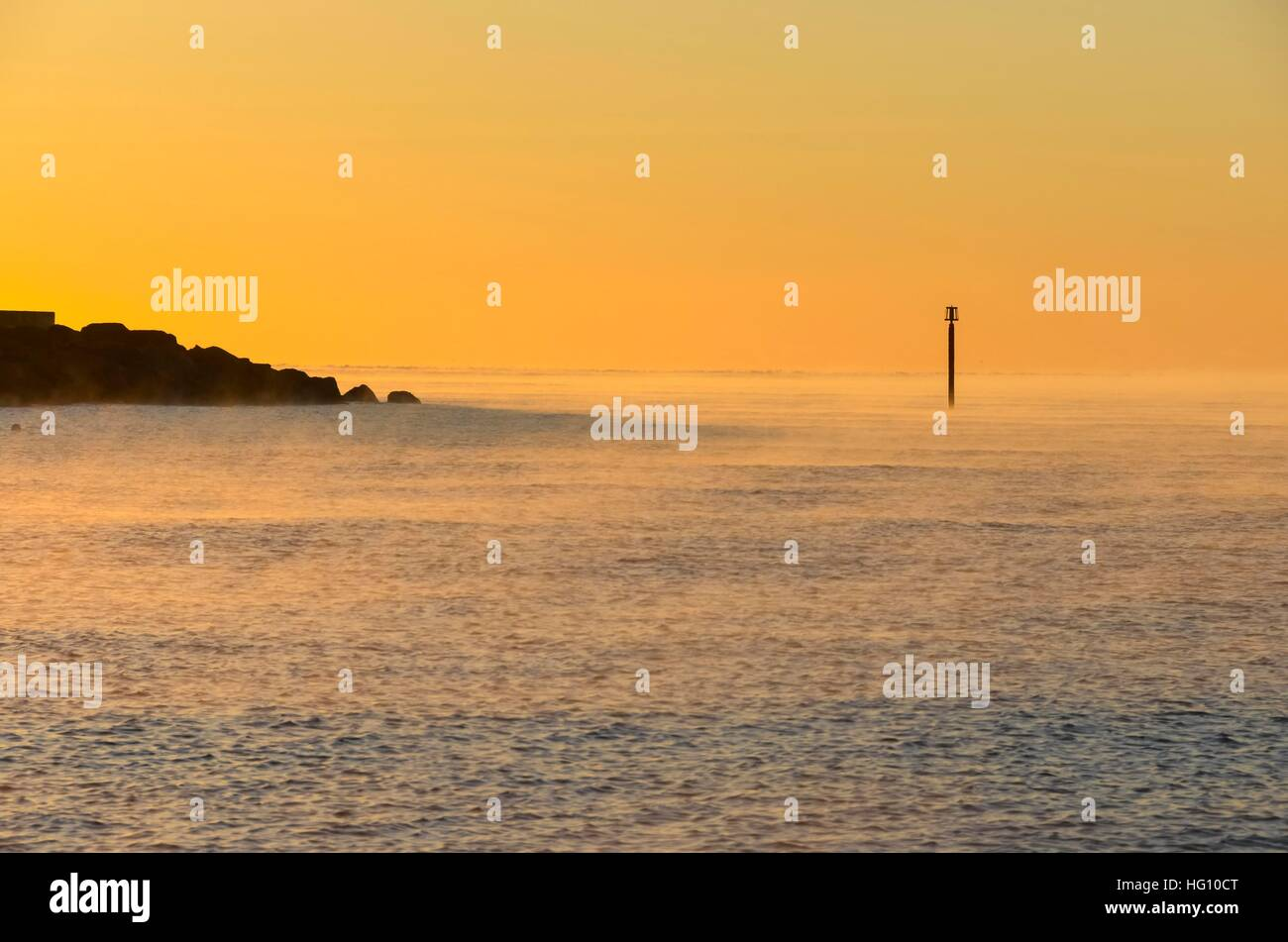 West Bay, Dorset, UK. 3rd Jan, 2017. UK Weather. Clear skies at sunrise with mist steaming of the surface of the - Stock Image