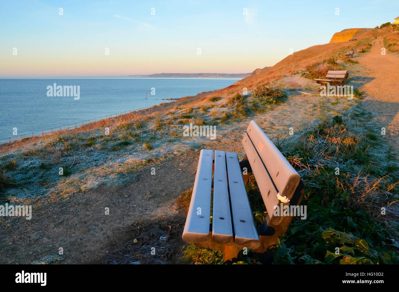West Bay, Dorset, UK. 3rd Jan, 2017. UK Weather. A frost covered bench with clear skies above at sunrise at West - Stock Image