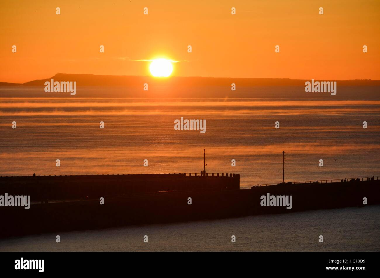 West Bay, Dorset, UK. 3rd Jan, 2017. UK Weather. Clear skies at sunrise with mist on the surface of the sea at West - Stock Image