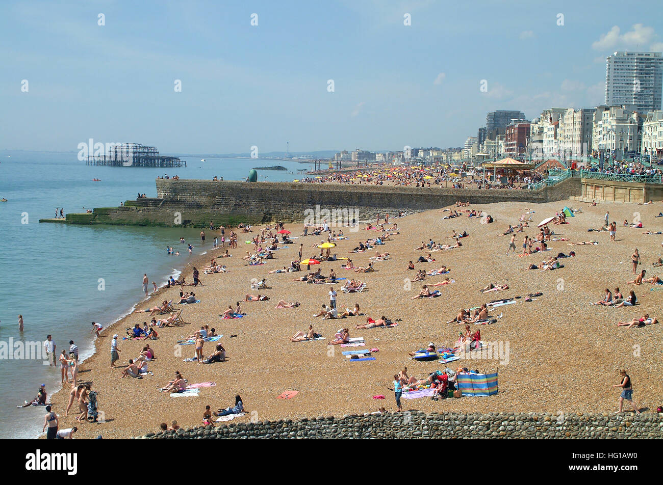 People on Brighton beach between sea defense groynes and the ruins of Old West pier in the background, Sussex, England. Stock Photo
