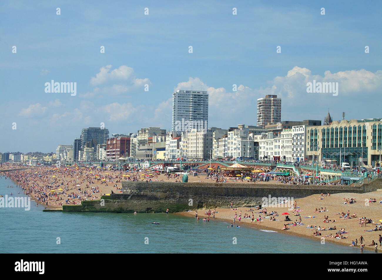 People on Brighton beach with hotels along the seafront, Sussex, England. Stock Photo