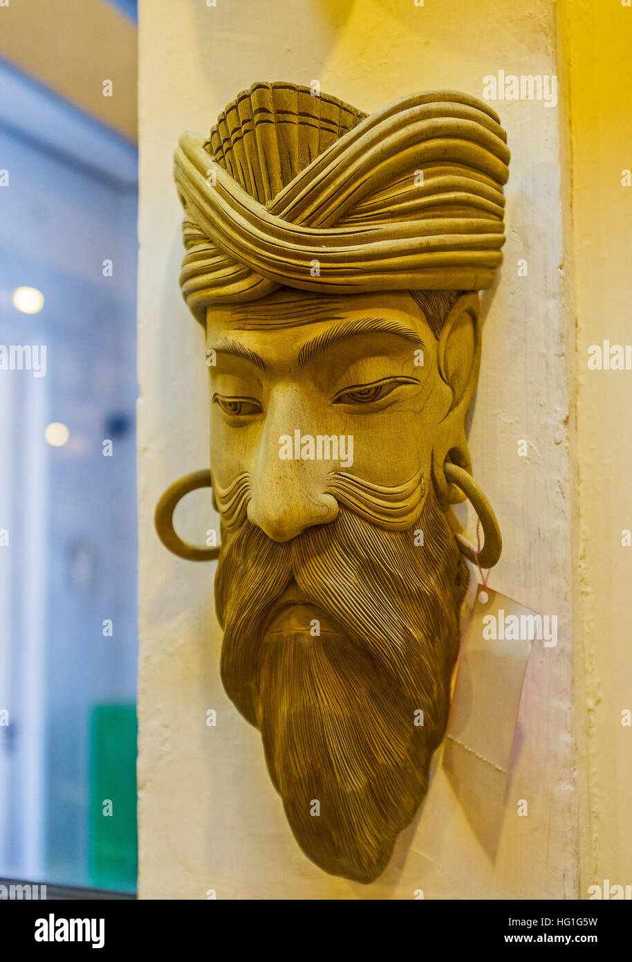 The wooden mask of a man on the wall of the mask store Stock Photo ...