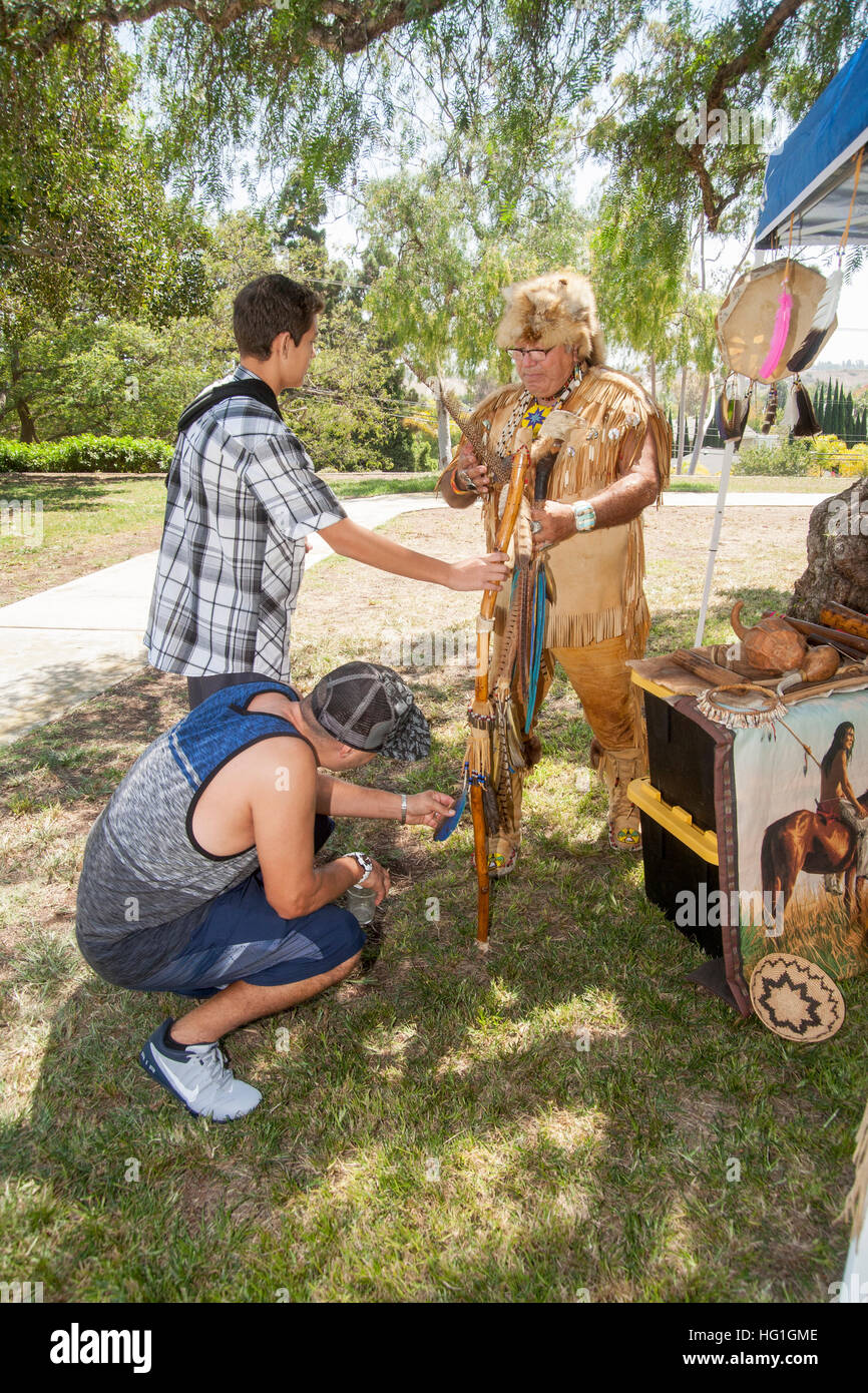 Dressed as an old time Native American Mission Indian, a historical re-enactor explains historical artifacts at - Stock Image