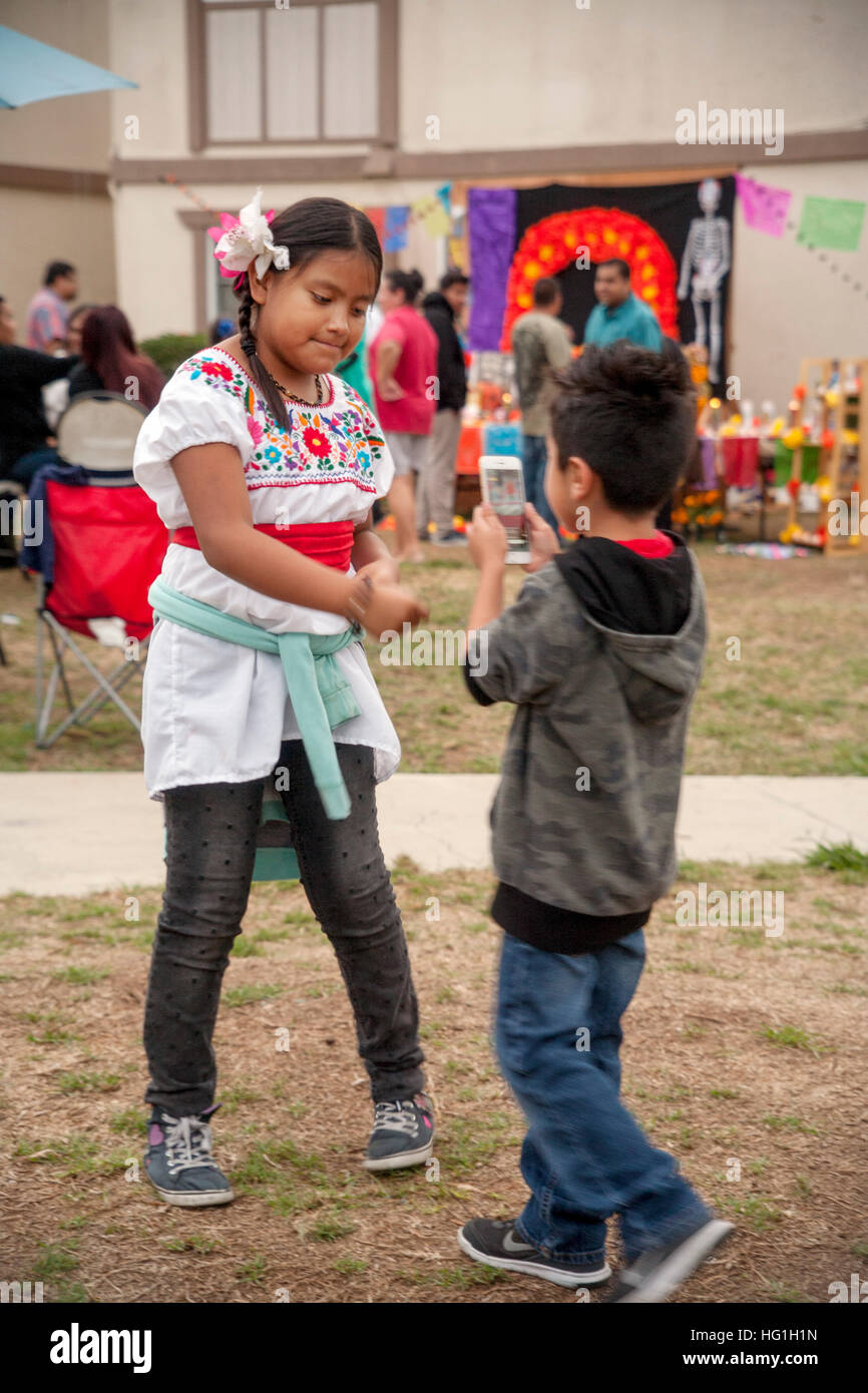 Local children in traditional clothing dance during preparations for Day of the Dead ceremonies in the courtyard - Stock Image