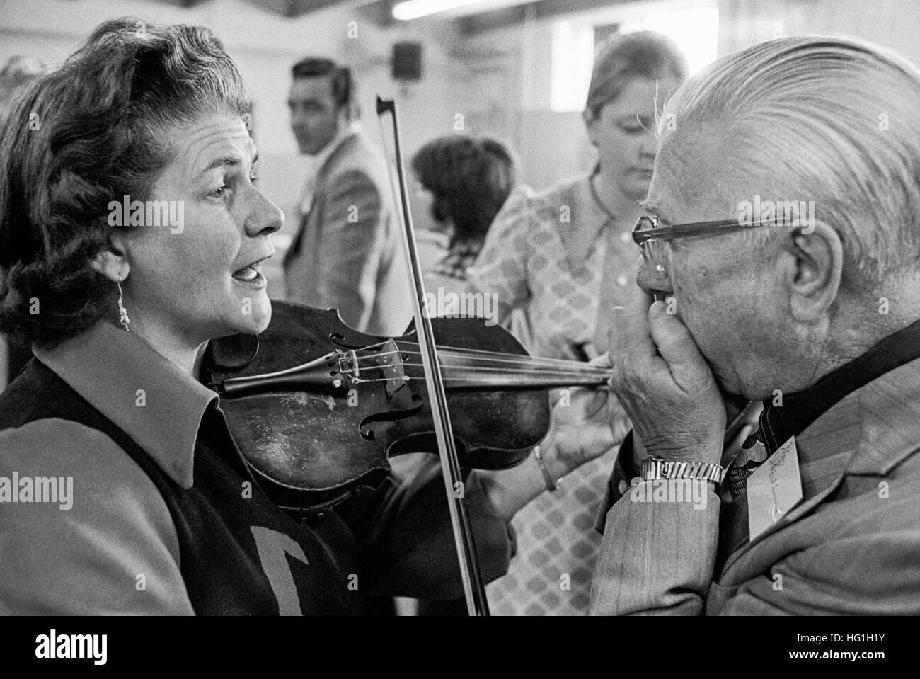 A woman violinist and an elderly male harmonica player rehearse backstage at a folk music festival and contest in - Stock Image