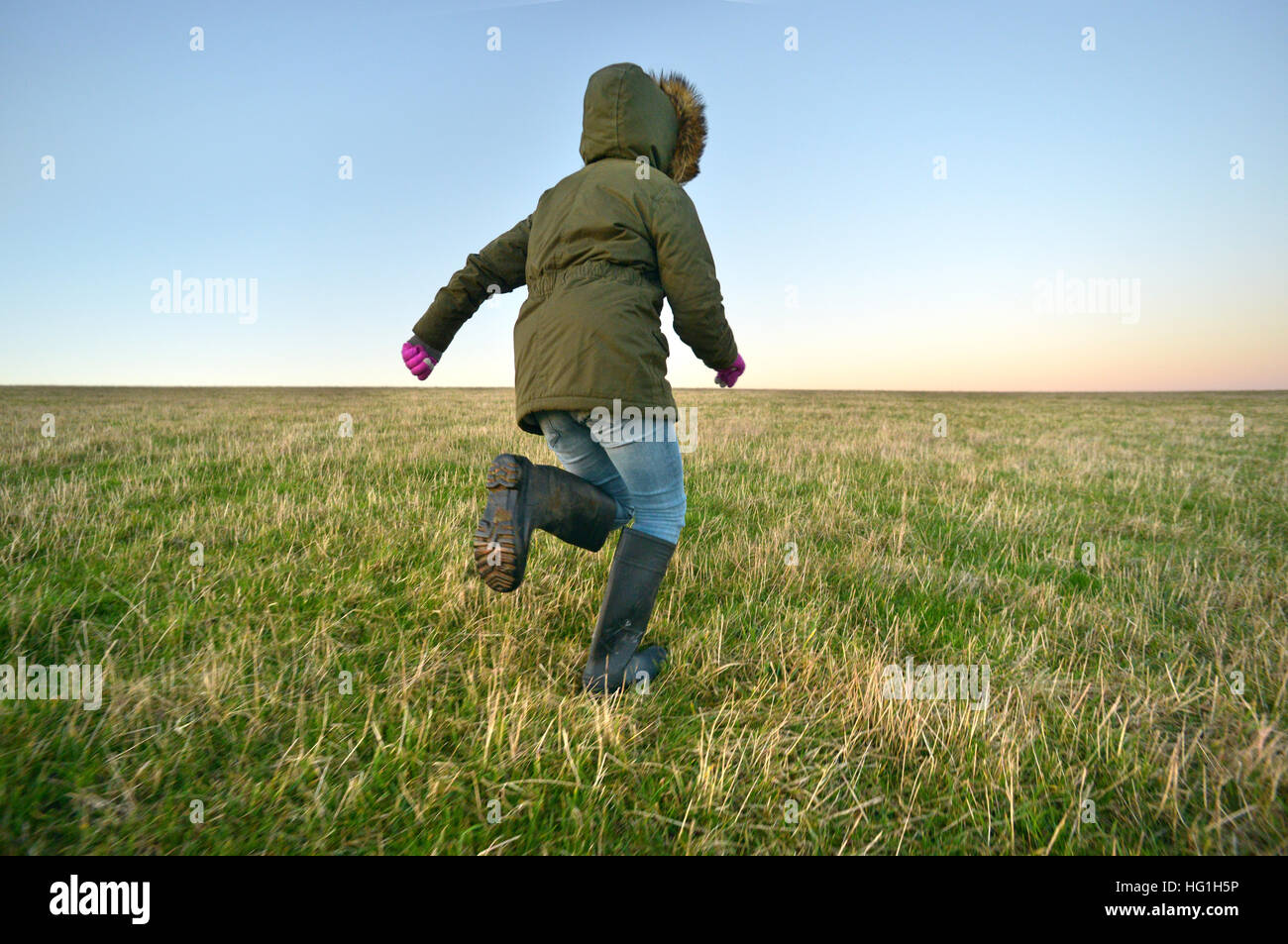 Child in welly boots running on a grassy hill - Stock Image
