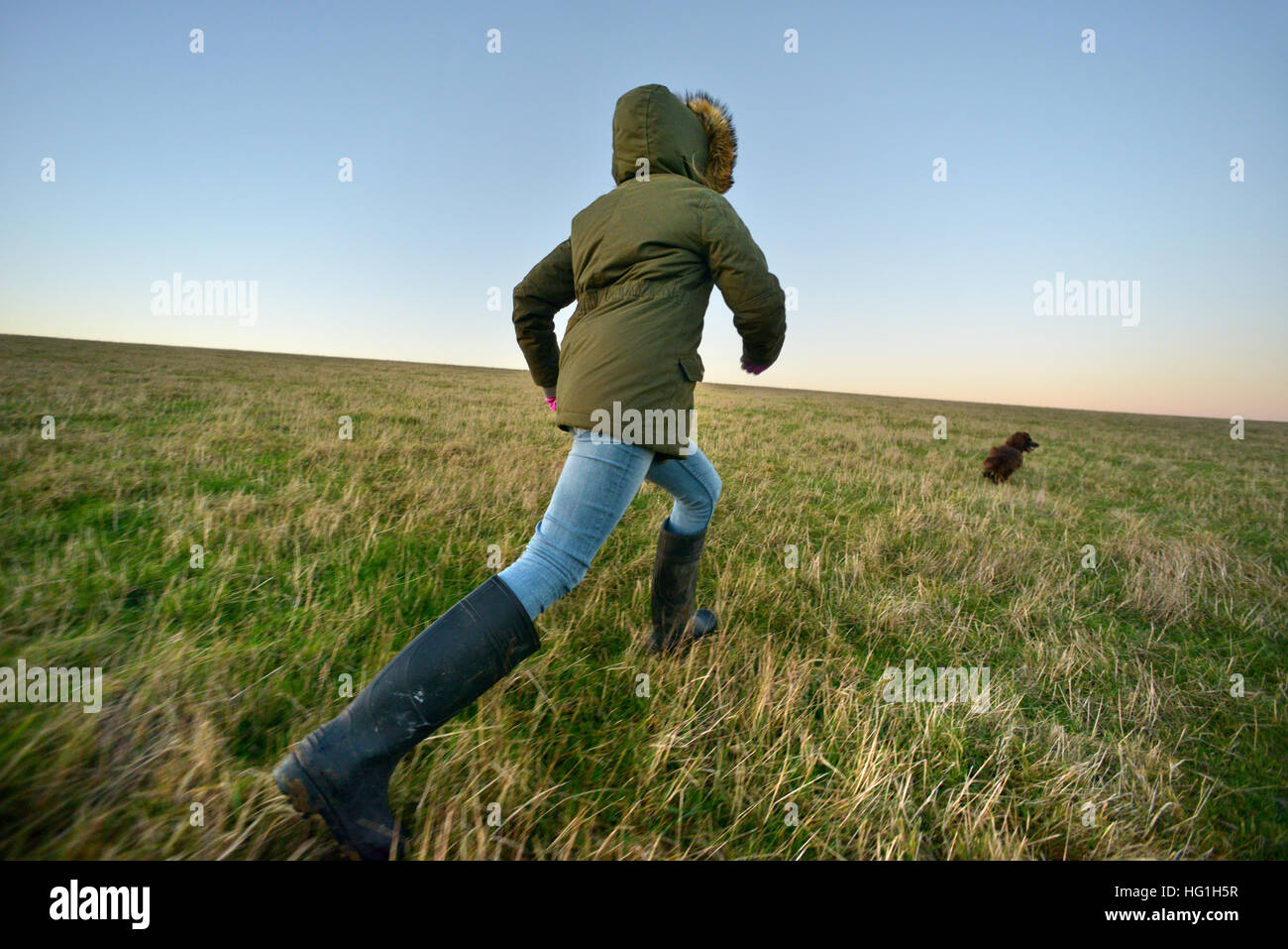 Child in welly boots running after a dog on a grassy hill - Stock Image