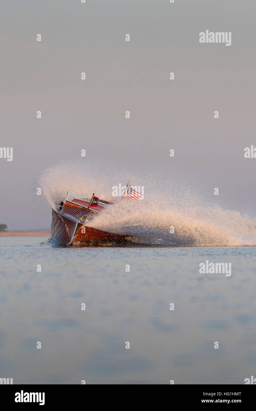An antique, wooden speedboat throwing spray in a fast turn. - Stock Image